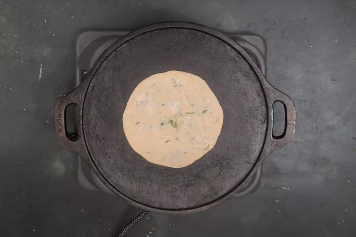 Paratha transferred on a hot griddle.