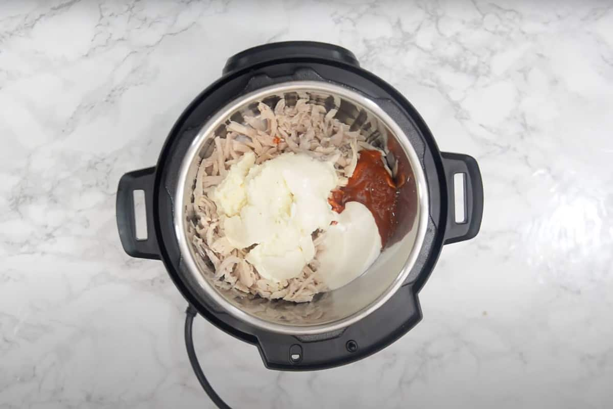 Unsalted butter, garlic, shredded chicken, buffalo wing sauce, cream cheese, and sour cream added in instant pot.