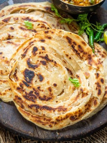 Lachha paratha or Lachedar paratha is a popular Indian bread made using whole wheat flour. It is just like your tawa paratha but with extra flaky and buttery layers. Check out 3 ways to make it at home.