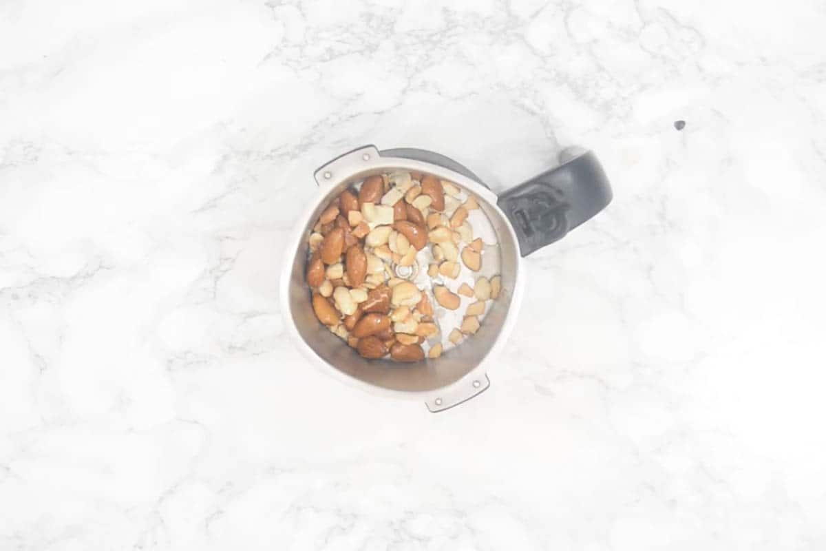 Roasted nuts added to a grinder.