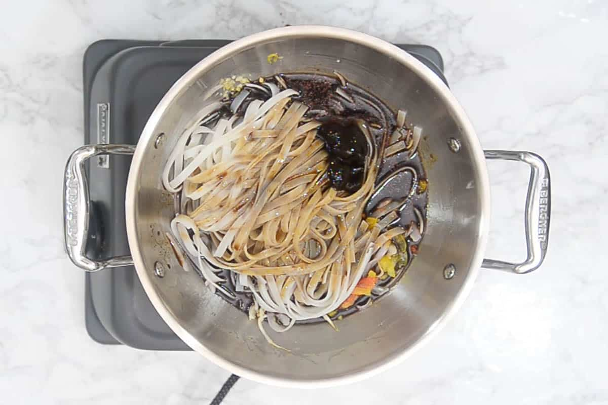 Cooked noodles and sauce added to the wok.
