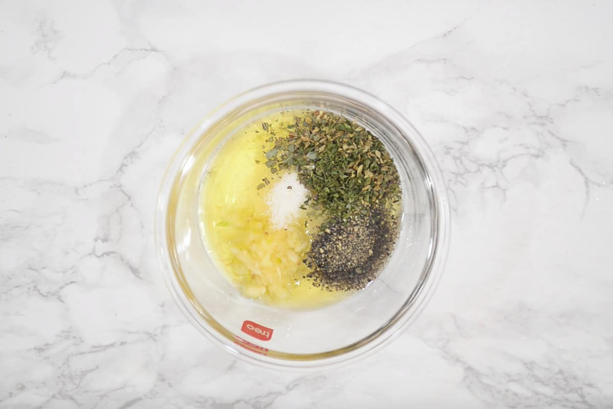 Garlic, herbs, salt, pepper and olive oil added in a bowl.