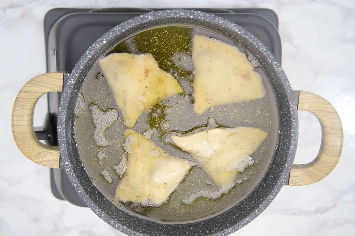 Samosa frying in oil.