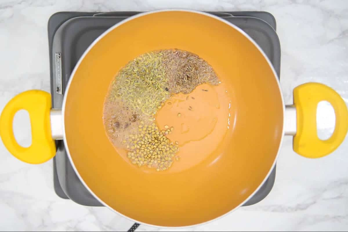 Asafoetida, cumin seeds, fennel seeds, and crushed whole coriander seeds added to the pan.