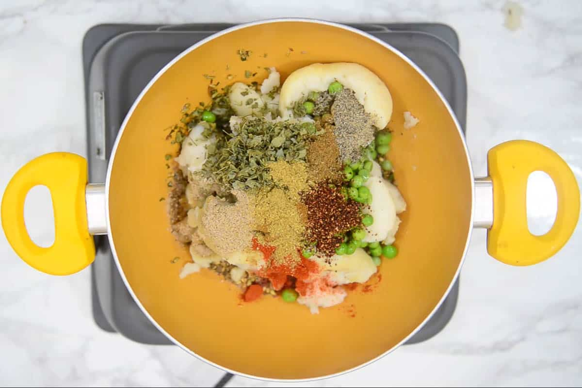 Kasuri methi, pomegranate seeds powder, cumin powder, garam masala powder, black pepper powder, dry mango powder, Kashmiri red chili powder, and coriander powder added to the pan.