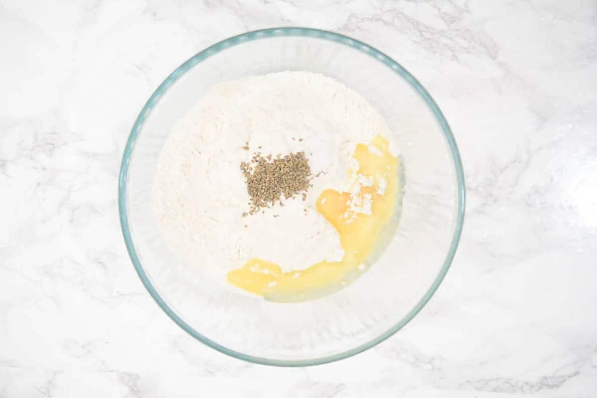 All-purpose flour, salt, ajwain, and vegetable oil aded in a bowl.
