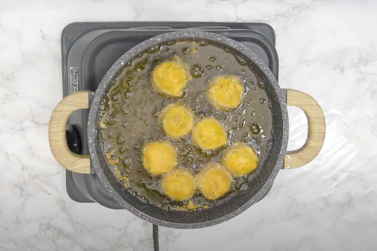 Batata vada frying for the second time in hot oil.