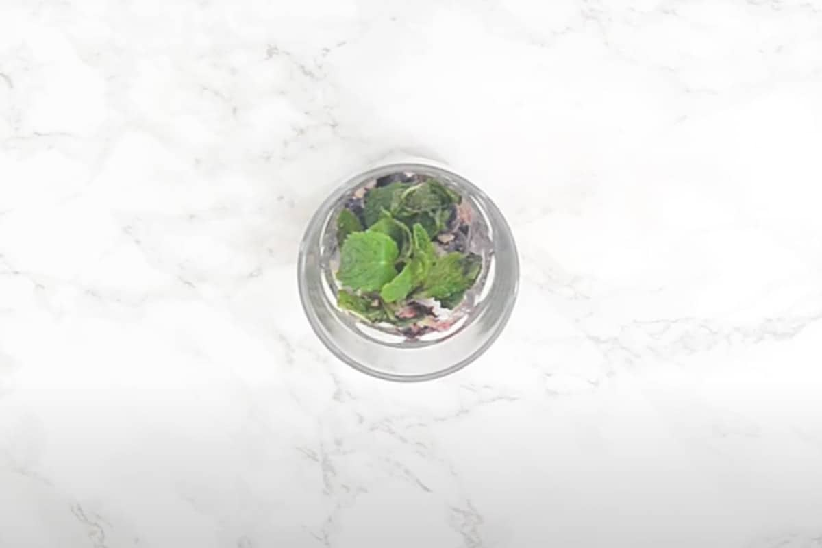 Mint leaves and sugar added in the glass.