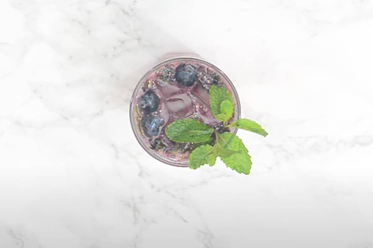 Ready blueberry mojito garnished with more blueberries and mint.