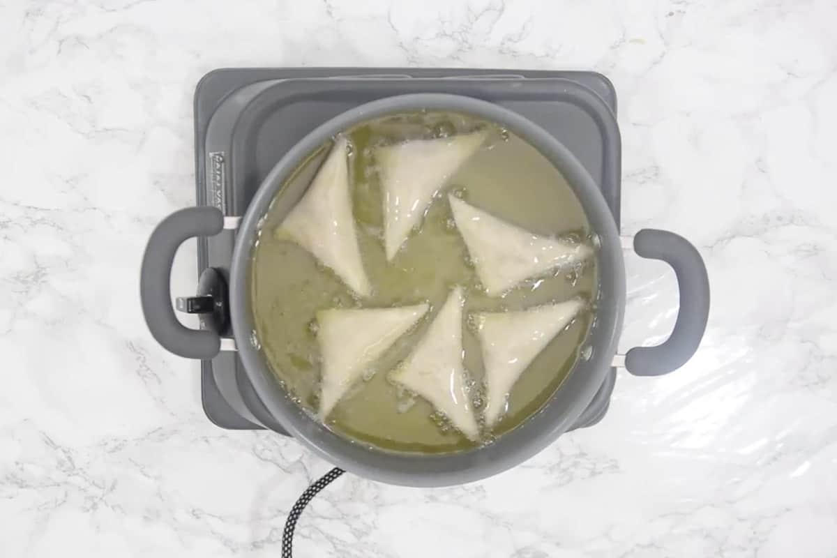 samosa frying in hot oil.