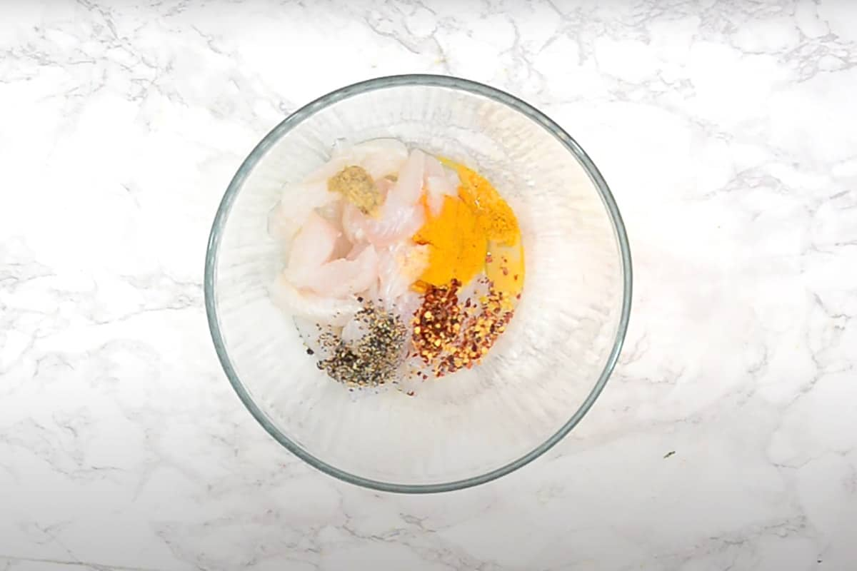 Fish mixed with salt, lime juice, turmeric powder, red chili flakes, black pepper and ginger garlic paste.