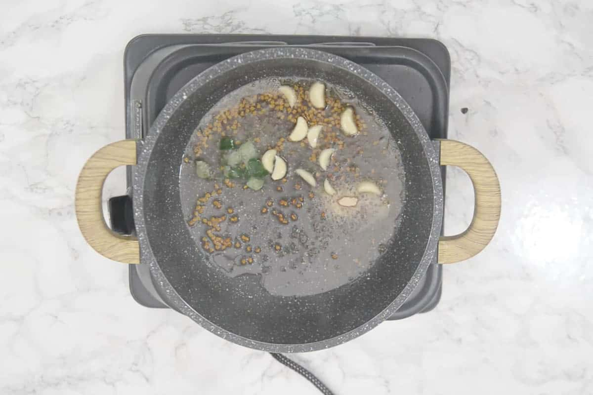 Asafoetida, curry leaves and garlic cloves added to the pan.