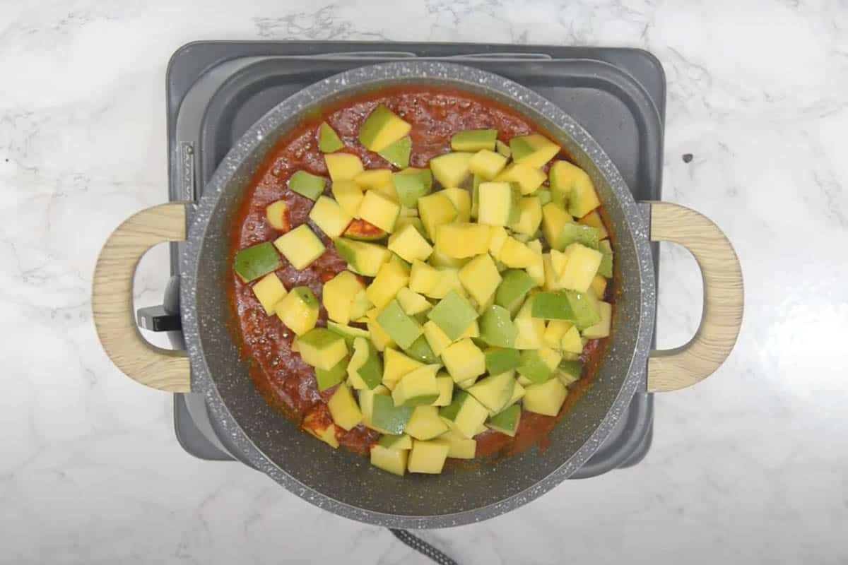 Mango cubes added to the pan.