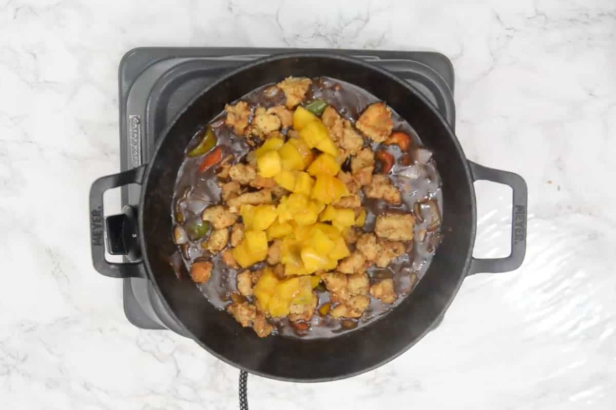 Fried chicken and mango added to the pan.