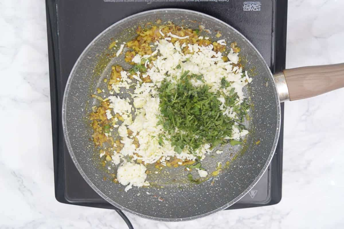 Grated paneer and coriander added to the pan.