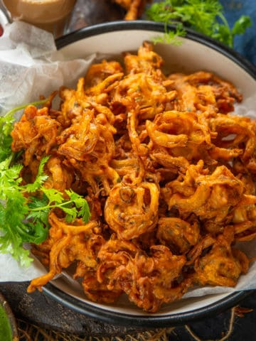Crispy Onion Pakora is one of the most favorite Indian snacks during Monsoons or Winter days. These fritters taste even better when served with some delicious Indian Chutneys.