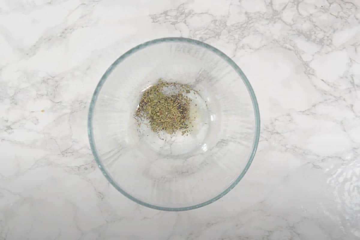 Extra virgin olive oil, salt, black pepper, dried rosemary and oregano mixed in a large bowl.