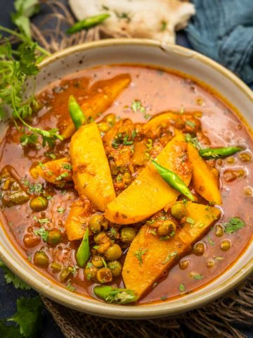Aloo Matar is a spicy North Indian curry made using potatoes, and green peas simmered in a deliciously spiced tomato sauce. This curry is vegan and gluten-free and comes together in under 30 minutes. Make it in a traditional pressure cooker or an Instant Pot.