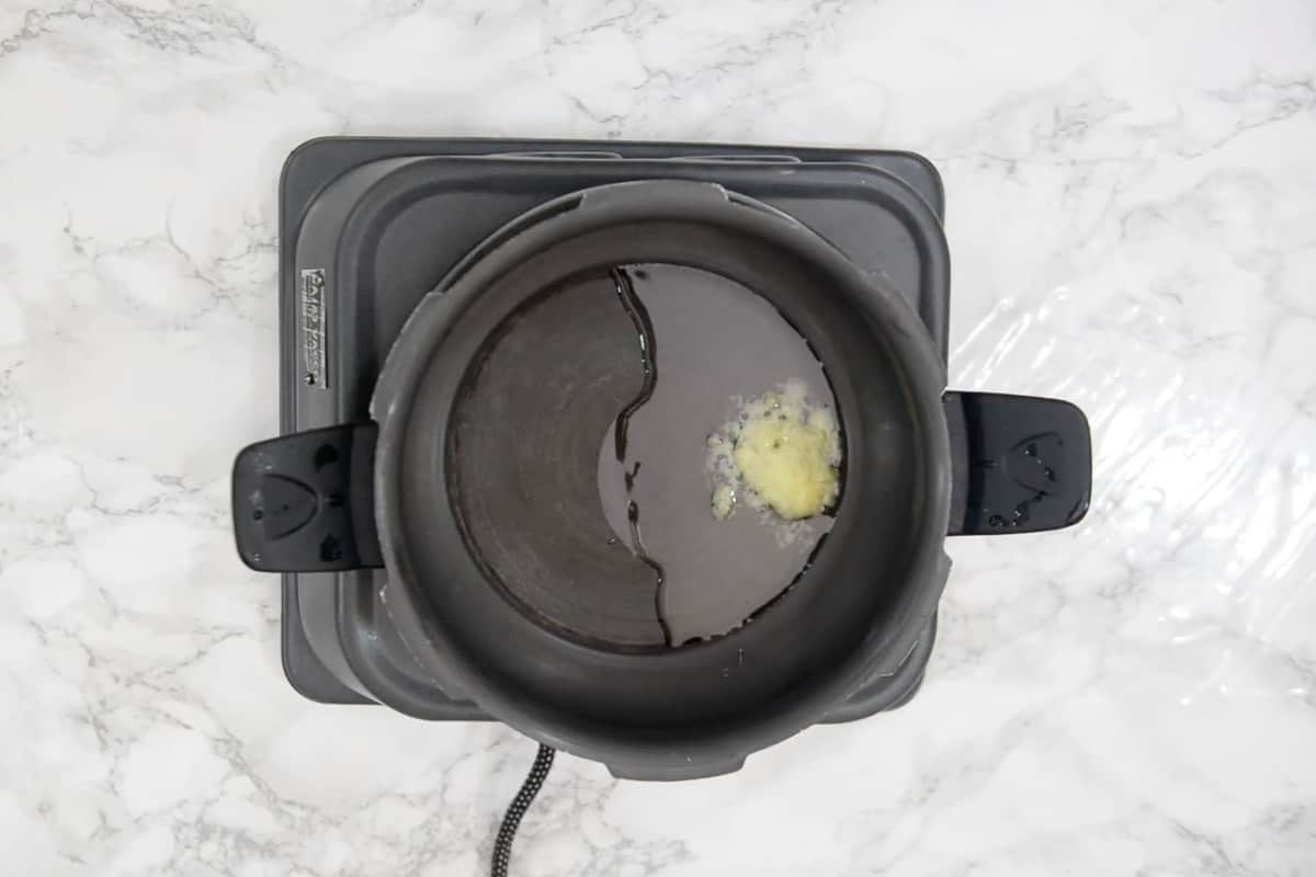 Oil and ghee heating in a pressure cooker.