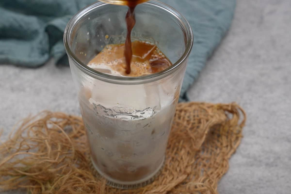Milk and espresso added to the glass.