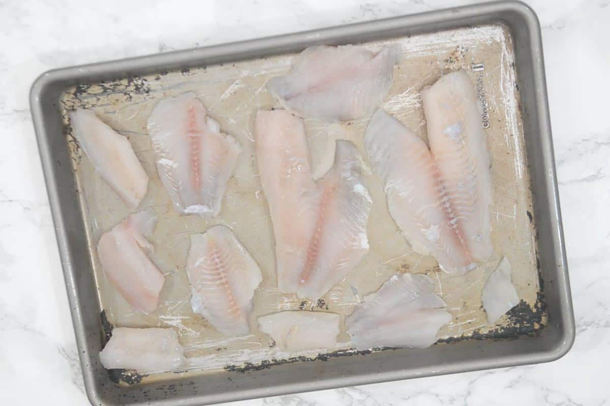 Tilapia fillets placed on a baking tray.