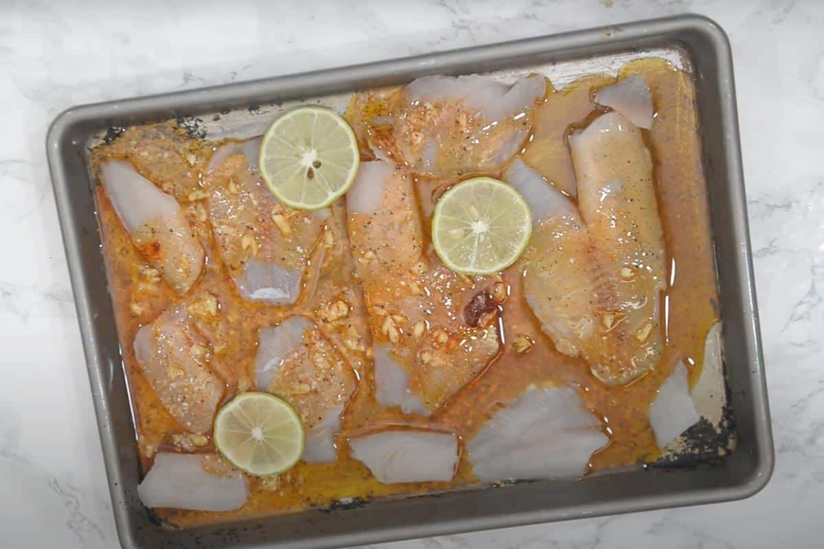 Marinade drizzled over the tilapia fillets.