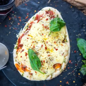 Easy, quick, and delicious, Naan Pizza is a fabulous variation of the classic pizza. Make it using frozen naan or make the naan from scratch, you are surely going to love this dish.