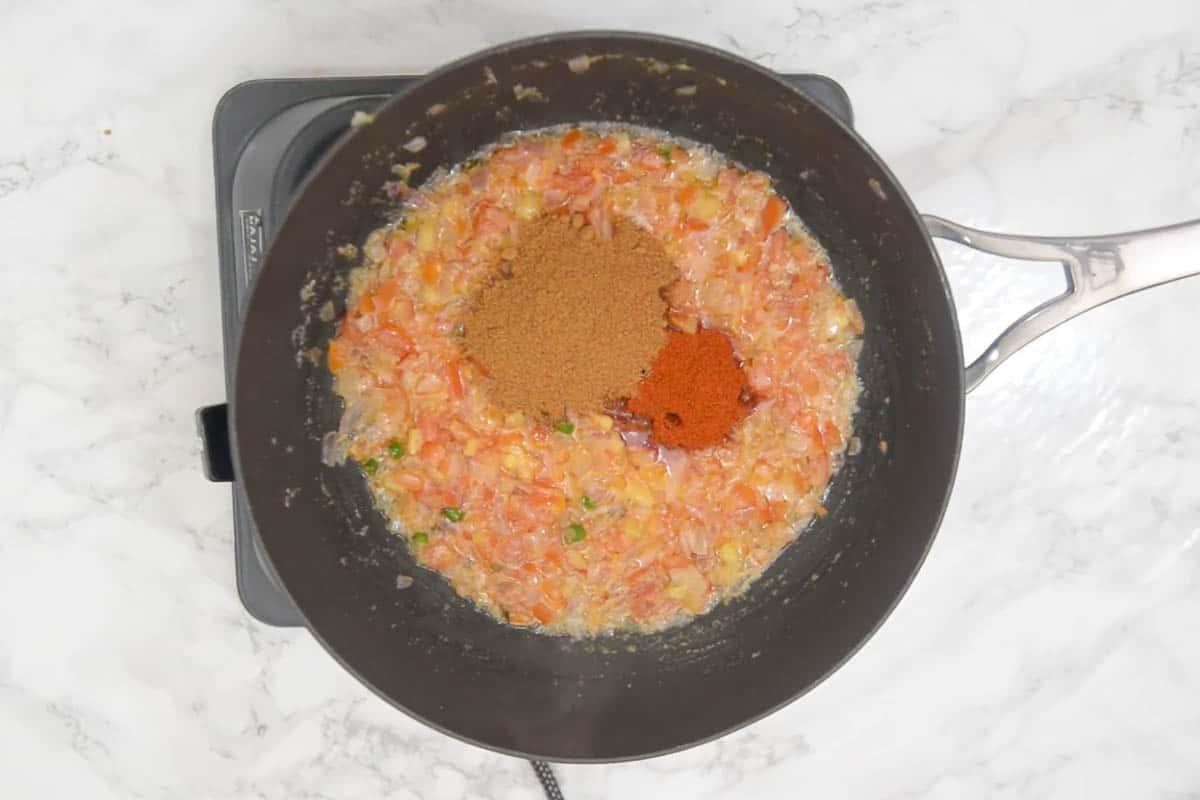 Red chili powder and pav bhaji masala added to the pan
