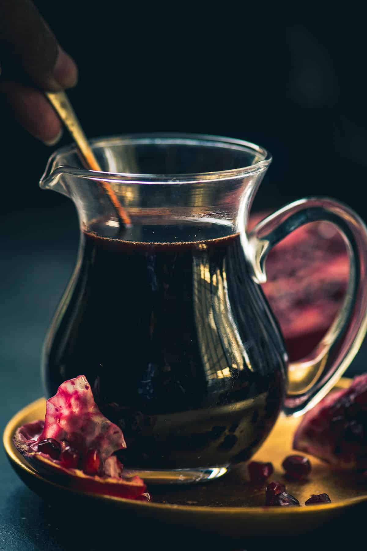 Pomegranate molasses served in a glass jar.