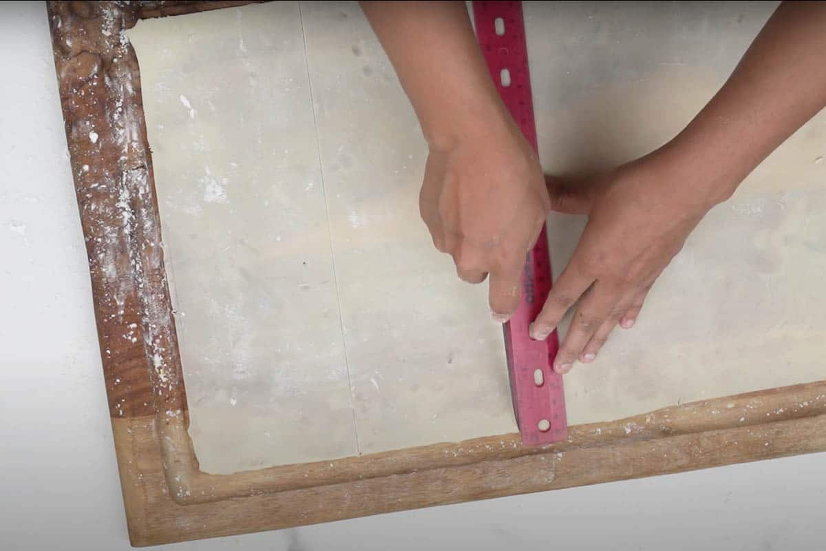 Measuring the rolled dough for cutting later.