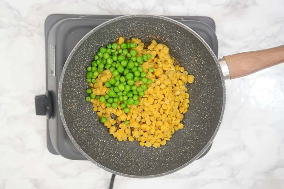 Cooked lentil and peas added to the pan.