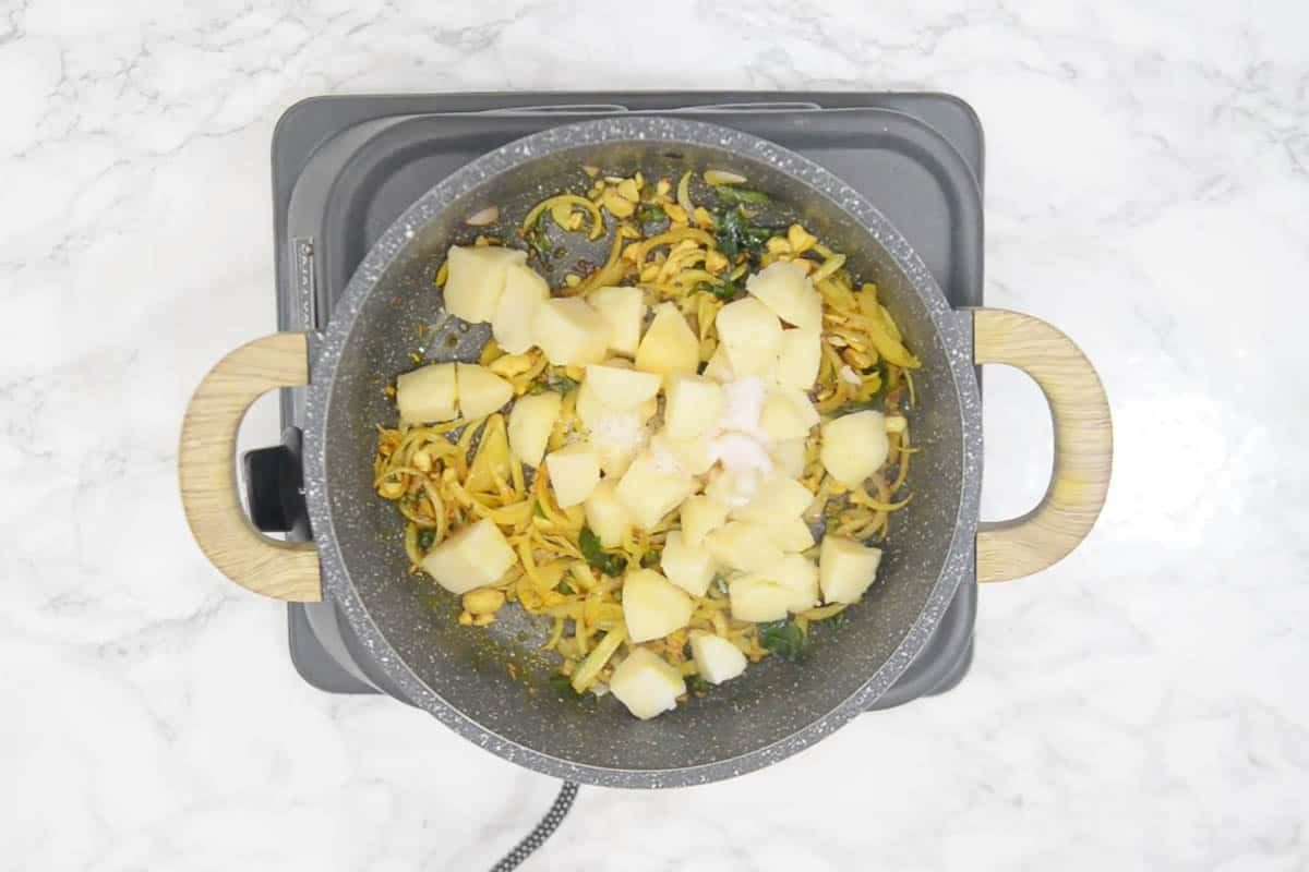 Boiled and cubed potato, salt and sugar added to the pan.