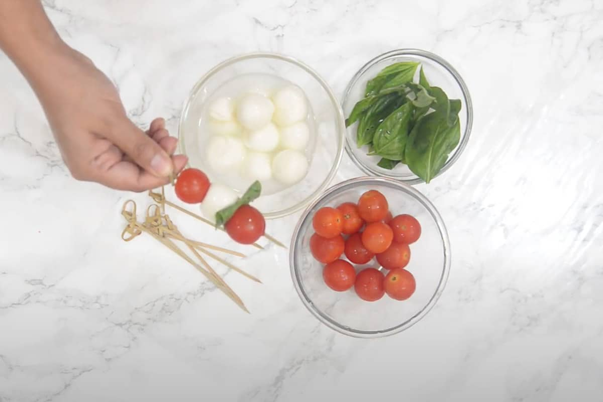Tomato, basil leaf and mozzarella ball threaded on a bamboo skewer.