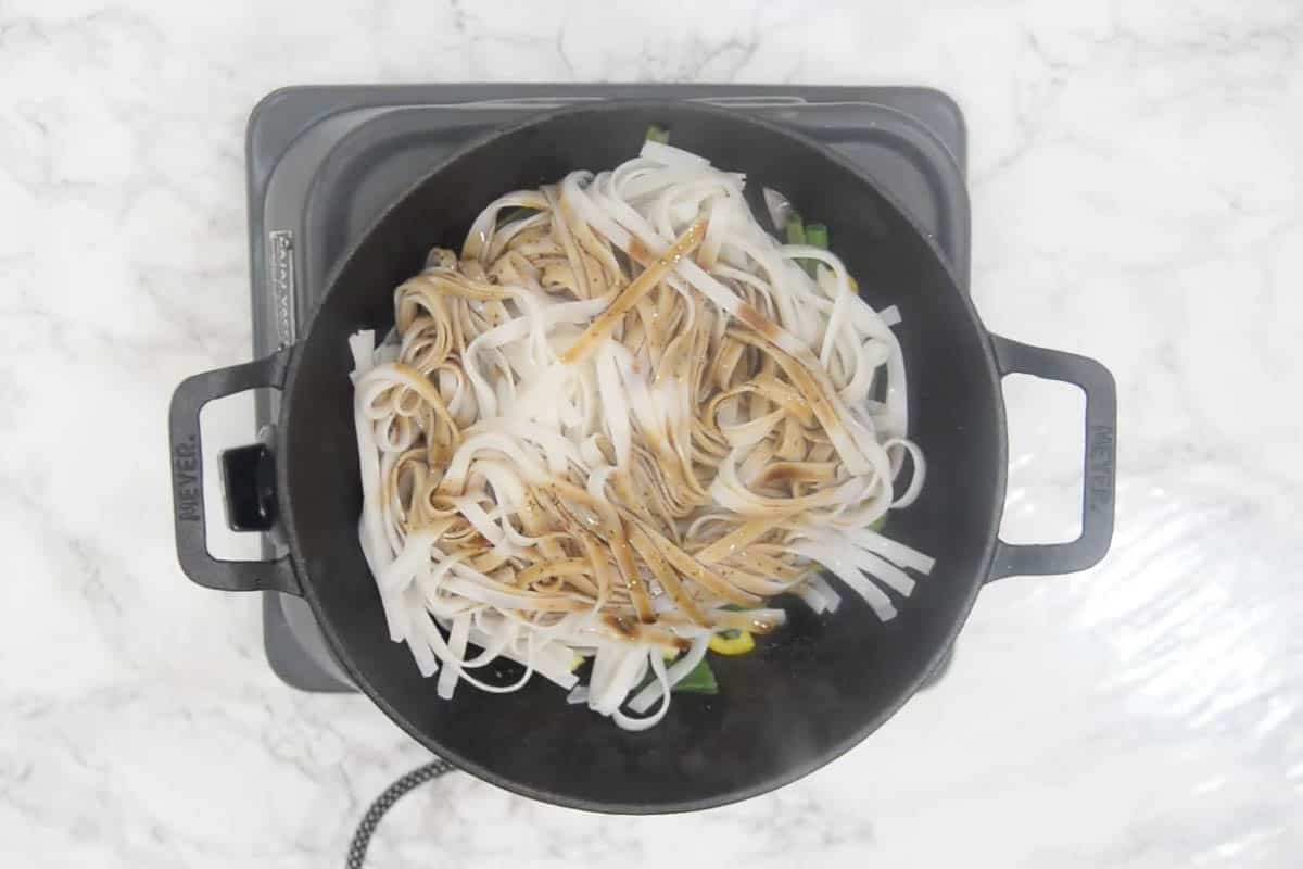 Cooked noodles and sauces added to the wok.