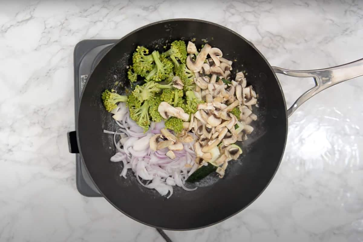 Zucchini, broccoli, onion and mushroom added in the wok.