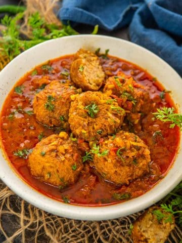 Lauki kofta is a delicious Indian curry made with bottle gourd dumplings (kofta) simmered in a spicy onion tomato based curry. Here is how to make it.