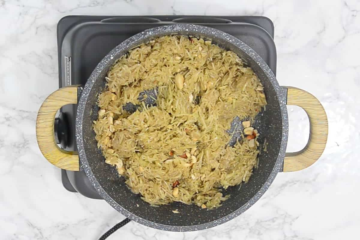 Grated lauki frying in ghee.