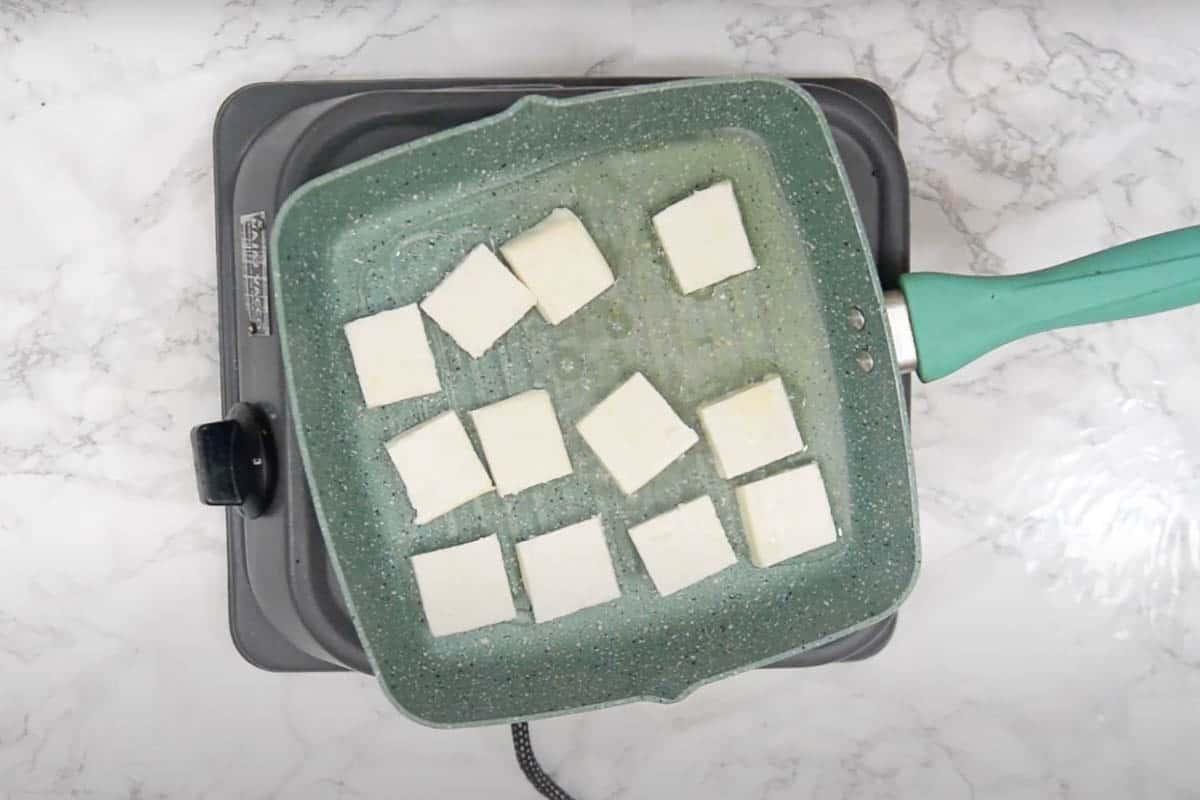 Paneer cubes frying in oil.