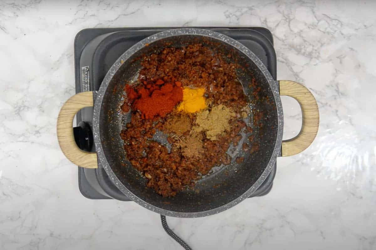 Dry spices added to the pan.