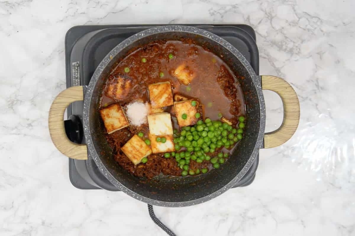 Paneer cubes and peas added to the pan.