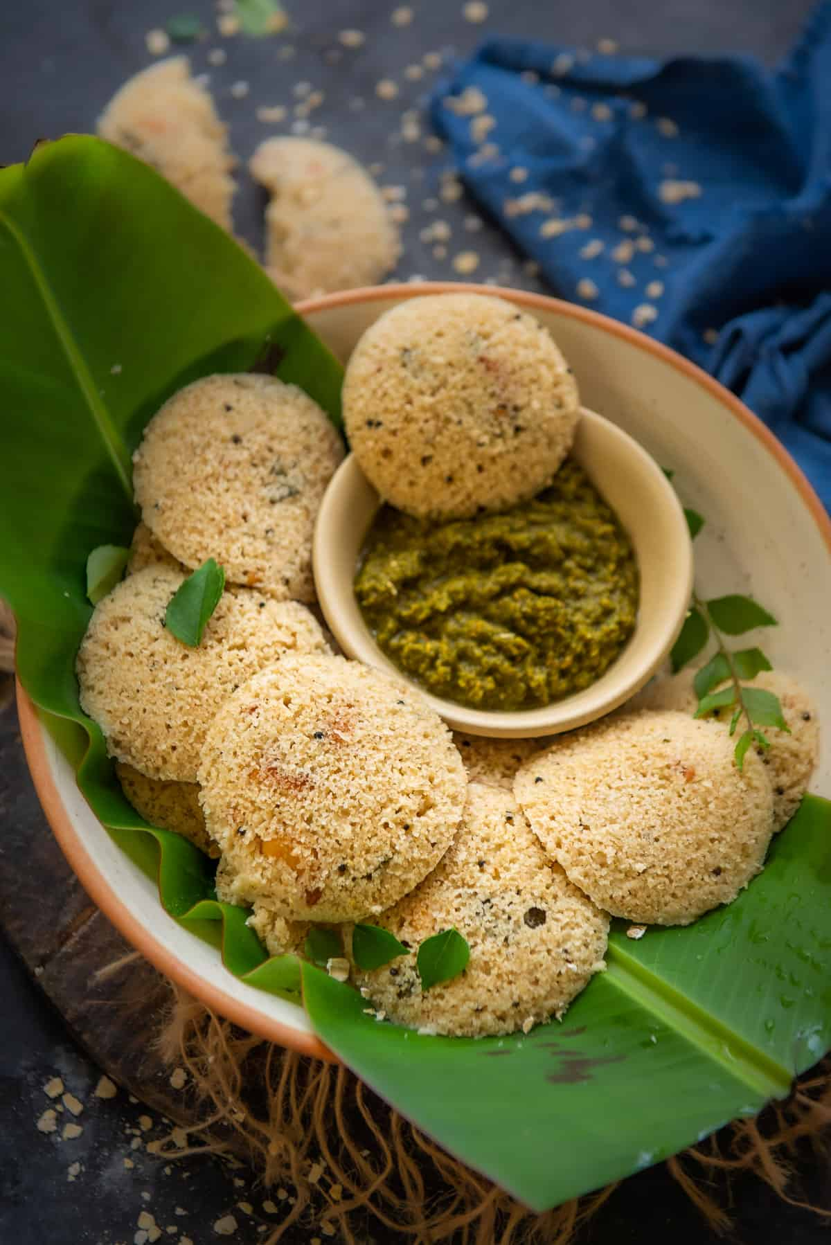 Oats Idli served in a bowl with chutney.