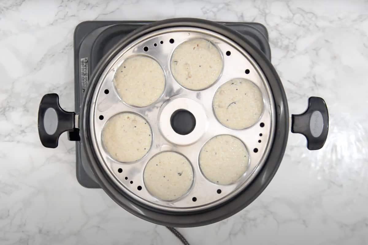 Idli mold kept over boiling water.