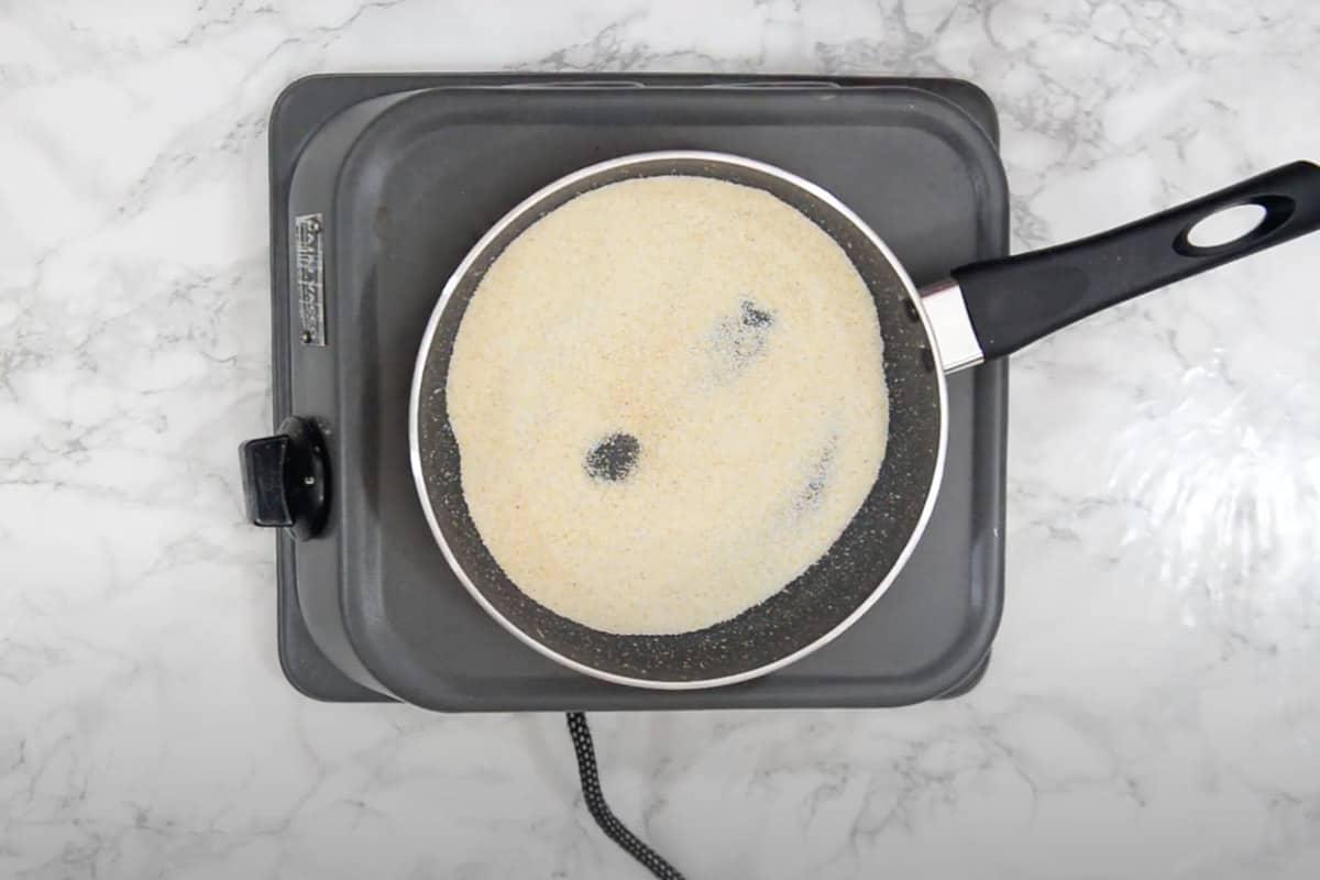 Semolina roasting in a pan.