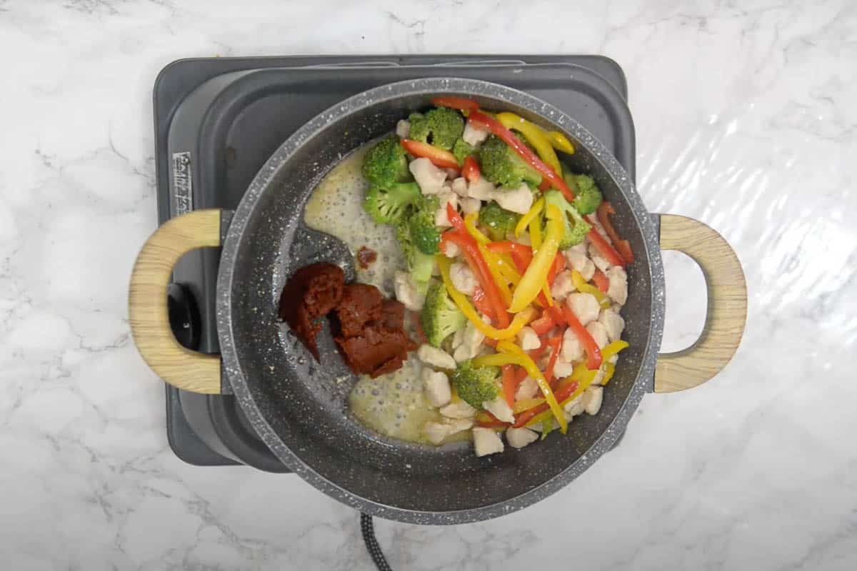 Panang curry paste added to the pan.