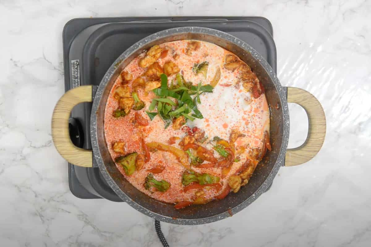 kaffir lime red chili, coconut milk and water added to the pan.
