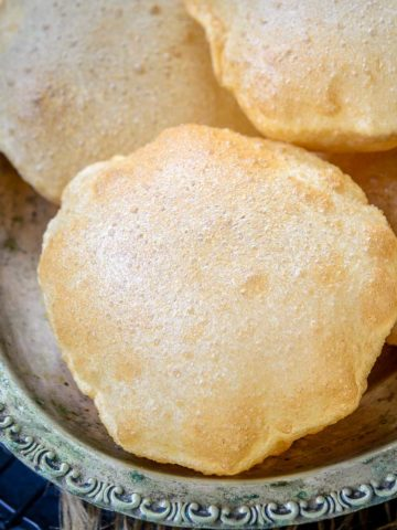Poori (Puri) is an Indian fried puffed bread that is made using whole wheat flour. This unleavened bread is soft, fluffy, and crispy and is perfect to serve with Indian curries. Check out my easy recipe to make perfectly puffed-up poori every single time.