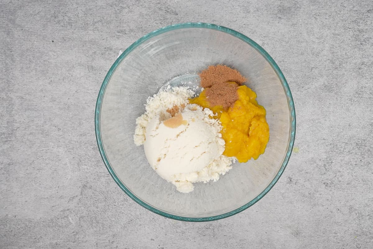 Pumpkin puree, vanilla pudding mix, pumpkin pie spice and vanilla extract added to a bowl.