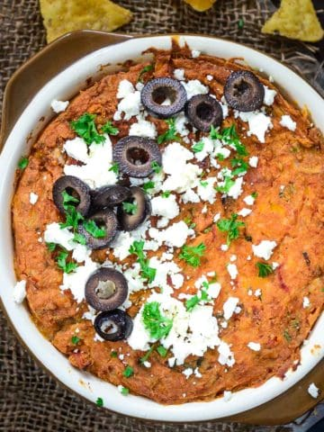 Refried Bean Dip is an easy-to-make hot dip that is great for parties or get-togethers. It is best served with nachos or chips, can be easily made from scratch, and comes together in 15 minutes.