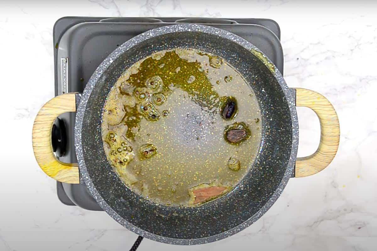 cloves, black peppercorn, black cardamom, and cinnamon in hot oil