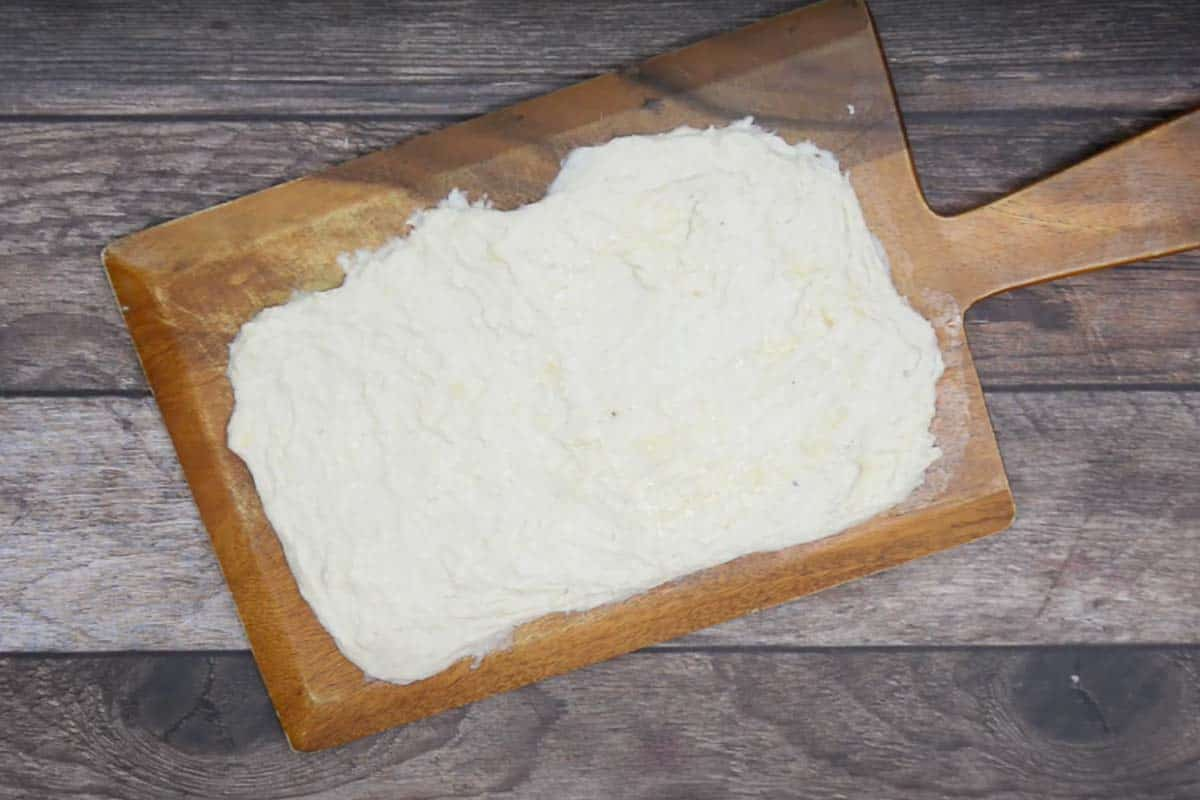 Dough stretched to make a rectangle and butter rubbed over it.